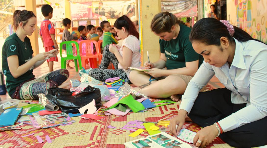 Volunteers working with children in Cambodia create educational resources to help the placement staff.
